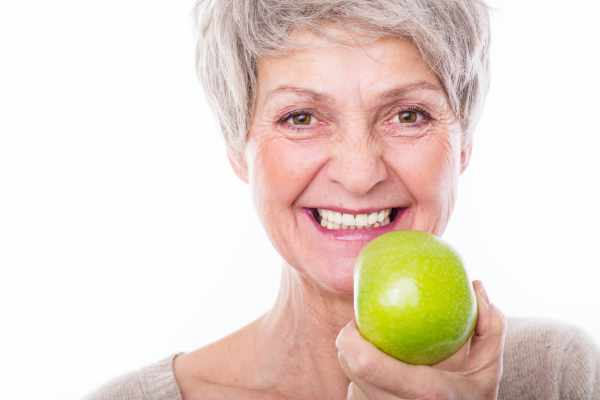 Smiling woman with apple showing off her hybrid dentures