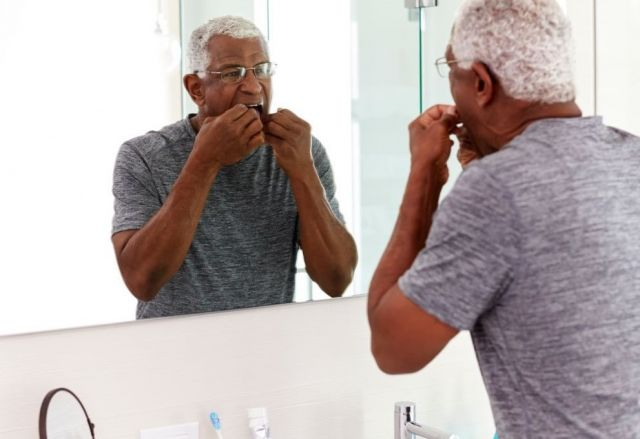 Older man flossing teeth in front of mirror - Novato, CA