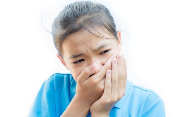 Girl with a blue shirt holding her mouth in pain because of a dry socket - Novato Oral Surgery, CA