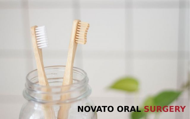 Two wood toothbrushes inside a clear glass jar - Novato, CA